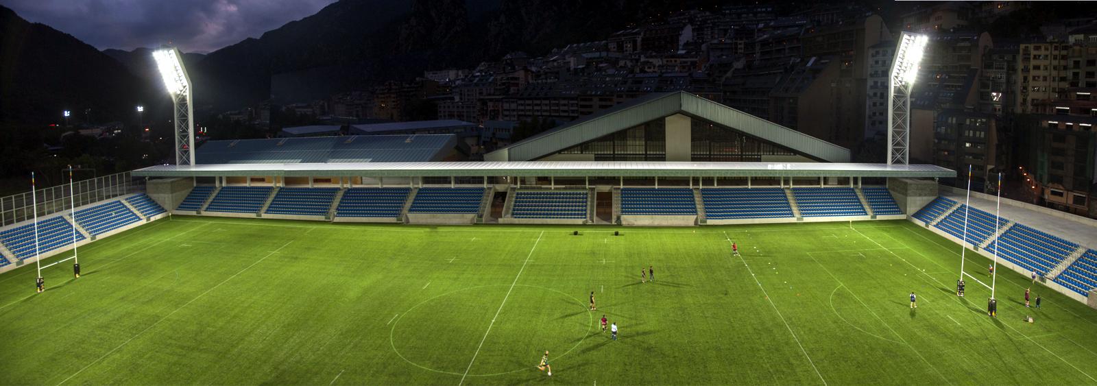 El nuevo Estadio Nacional de Andorra se encaja en un espacio realmente estrecho frente al río Valira. Los edificios deportivos que lo rodean son muy voluminosos y el resto de edificaciones que ocupan la montaña dan un marcado carácter vertical y constreñido al lugar. La anchura del solar es de 85 metros y se debe situar un terreno de juego libre de 130x80 metros. Con estas premisas se propone un edificio bajo, que no quiera competir en altura precisamente para destacar, dándole valor al vacío. Sin embargo, se propone cubrir la calle de servicio que separa el campo de los dos pabellones deportivos, como estrategia para conseguir situar las gradas de tribuna mirando a levante. Con esta decisión conseguimos, al mismo tiempo, reducir perceptivamente la altura de los dos edificios deportivos en unos 4 metros. Esta misma plataforma de cubrimiento es el gran puente-plaza sobre el río Valira y el acceso natural del público desde la avenida Salou. Desde esta cota, bajan seis niveles de gradas hasta el terreno de juego rodeando tres lados del campo situando 3.000 espectadores en una primera fase. Estas gradas son en realidad una depresión de la gran plataforma de acceso al campo. El edificio principal de servicios queda bajo este nivel en el extremo opuesto al río, con acceso por la Baixada del Molí a modo de zócalo del Estadio. Las fachadas principales de el Estadio están en los dos goles norte y sur, y se apoyan sobre la gran plataforma de acceso. Son de vidrio translúcido y ocupan un espesor de un metro permitiendo ubicar en su interior unas gradas retráctiles que posibilitan ampliar el aforo del Estadio en 1.850 personas más, haciendo un total de 4.850 espectadores sentados entre las dos fases. Estas gradas retráctiles alojadas al grueso de la fachada, pretenden que el edificio no altere su volumen ni su presencia urbana cuando deba hacerse la ampliación para la segunda fase y, al mismo tiempo, consiguen que el Estadio no se vea demasiado vacío en un aforo cotidiano más n